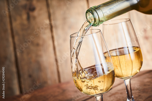 Photo sur Aluminium Bar Dispensing golden white wine into two wineglasses