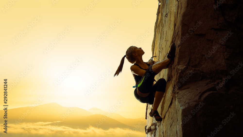 Fototapety, obrazy: Beautiful Woman Climbing on the Rock at Foggy Sunset in the Mountains. Adventure and Extreme Sport Concept