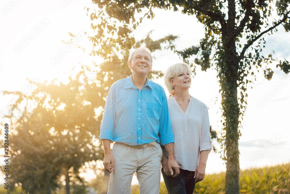 Fototapeta Senior woman and man having a walk along path in the countryside