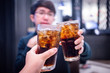 canvas print picture - Young couple with glasses of refreshing cola with ice in restaurant, Two glasses of cola with ice