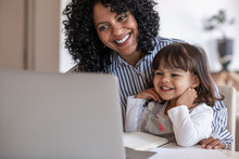 Busy Mother And Entrepreneur Using A Laptop With Her Daughter