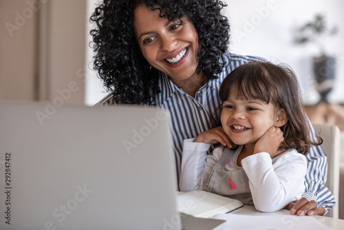 Obraz Busy mother and entrepreneur using a laptop with her daughter - fototapety do salonu