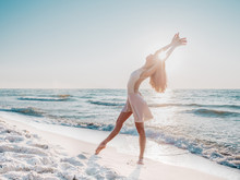 Slender Beautiful Ballerina In White Dress Dancing Ballet On Sea Or Ocean Sandy Beach In Morning Light. Concept Of Art, Nature Beauty