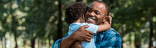 Panoramic Shot Of Happy African American Father Hugging Son