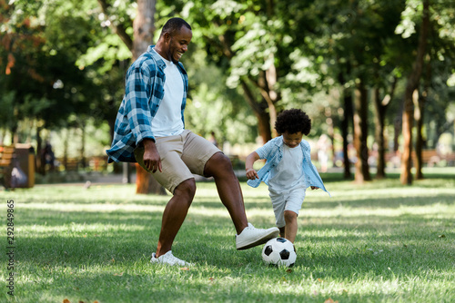 Fototapeta happy african american man playing football with curly son