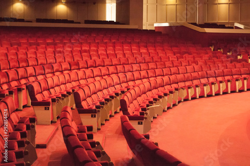 Rows of red cinema seats. View of empty theater hall. Comfort chairs in the modern theater interior