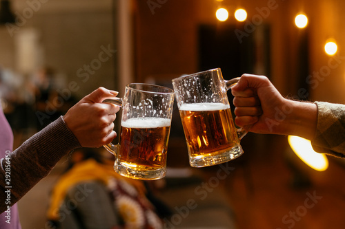 Fotomural  Close-up of two people toasting with beer.