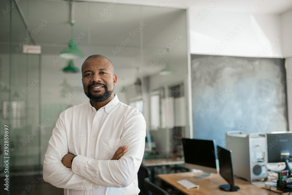 Fototapeta Smiling African American businessman standing alone in a large office