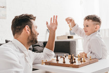 Dad And Son Playing Chess Together At Home