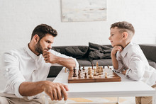 Dad And Son Playing Chess Toge...