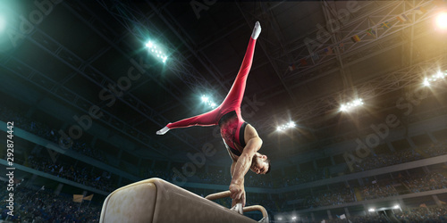 Photo Male athlete doing a complicated exciting trick on a Pommel horse in a professional gym