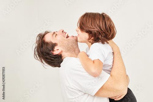 Glücklicher Vater umarmt lachend seinen Sohn - 292877053