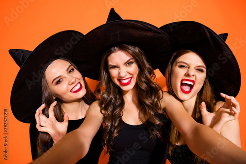 Photo  Closeup photo of three cruel witch ladies making selfies showing evil facial exp