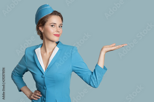 Beautiful stewardess holding blank on her hand. Blue background. Wallpaper Mural