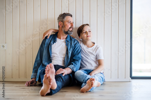 Mature father with small son sitting indoors, talking. Canvas Print