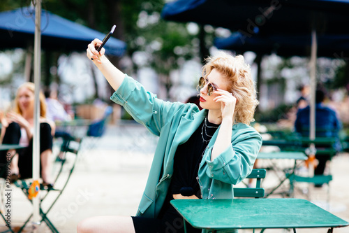 Fototapeta Woman sitting at table outside taking selfie obraz