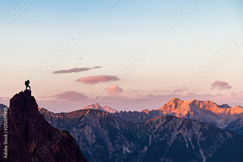 Obraz Hiker on top of a Mountain Looking to the Sunset - fototapety do salonu