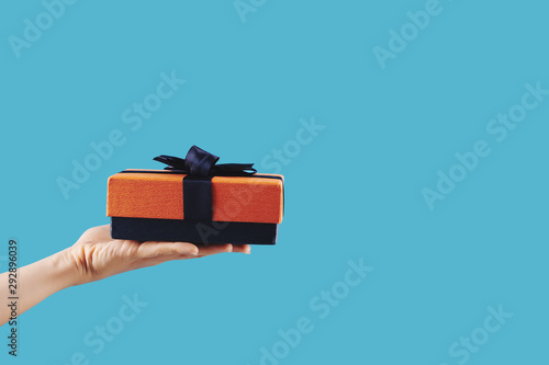 Photo sur Toile Ecole de Danse Small gift wrapped in blue and orange paper in hand of person, isolated on blue