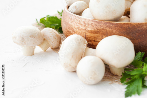 Fotografie, Tablou  Fresh mushrooms champignon in brown bowl on white background.