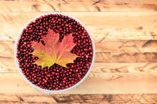 The Full Bucket Of Cranberries (Oxycoccus) Is On Wooden Background, Top View.