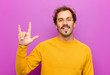 canvas print picture - young handsome man feeling happy, fun, confident, positive and rebellious, making rock or heavy metal sign with hand against purple wall