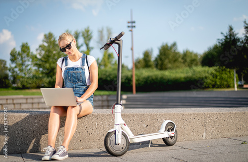 Modern woman using her laptop computer while sitting at street with electric scooter