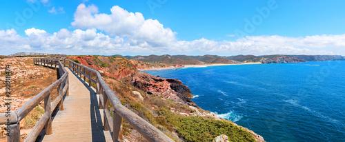 Montage in der Fensternische Blau traumhaft schöner Küstenwanderweg mit Holzsteg an der Costa Vicentina, Algarve Portugal