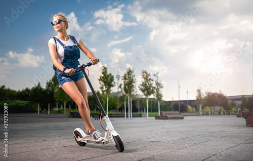 Full lenght shot woman riding an electric scooter, modern generation
