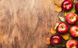 canvas print picture - Autumn food background. Ripe apples with nuts, fallen leaves and cinnamon on rustic wooden table. Top view. Copy space