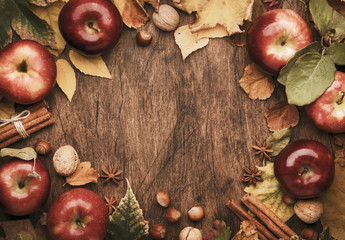 Autumn food background. Ripe apples with nuts, fallen leaves and cinnamon on rustic wooden table. Top view. Copy space