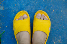Feet Of A Man Wearing Sandals Or Flip Flops On The Concrete Floor.