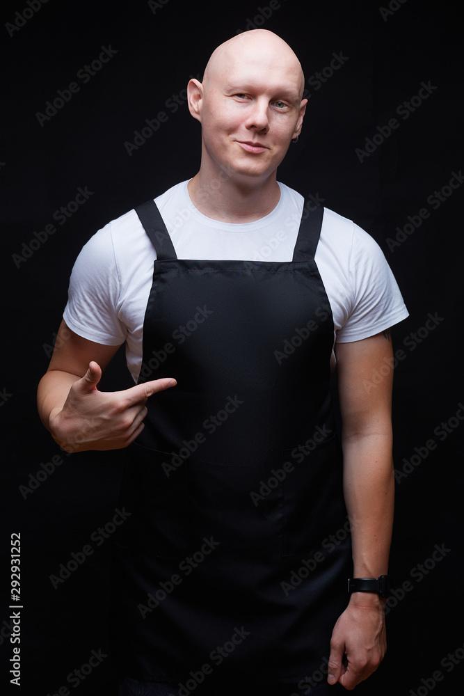 Fototapeta Strong handsome smiling bald guy wearing black apron pointing his finger on his chest. Butcher, baker, chef or waiter concept. Mockup for restaurants, grossery shops, bakery, butchery.