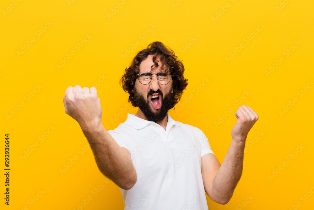Fototapety, obrazy: young crazy man shouting triumphantly, looking like excited, happy and surprised winner, celebrating against yellow wall