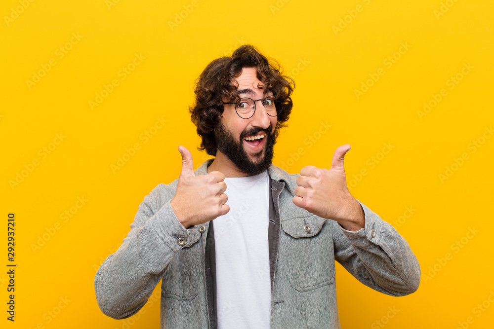 Fototapeta young crazy man smiling broadly looking happy, positive, confident and successful, with both thumbs up against yellow wall