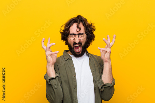 Fotografie, Obraz young crazy man screaming with hands up in the air, feeling furious, frustrated,