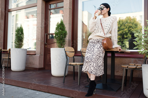 Stampa su Tela fashion woman in sunglasses and a warm knitted sweater is drinking coffee