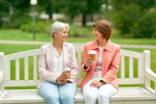 Old Age, Retirement And People Concept - Two Senior Women Or Friends Drinking Coffee And Talking At Park