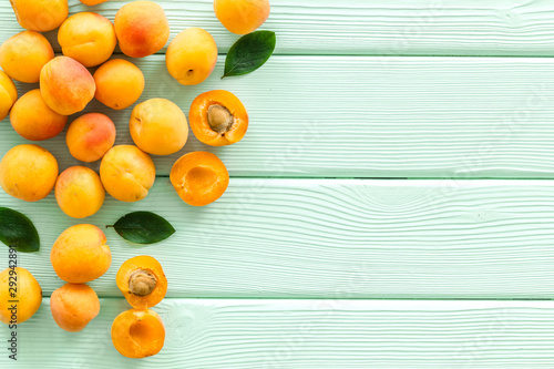 Fruit frame. Apricots and leaves on green wooden background top view space for text - 292942891