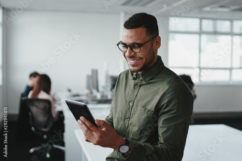 Obraz Smiling young businessman touching smartphone and checking online information in the modern office - fototapety do salonu