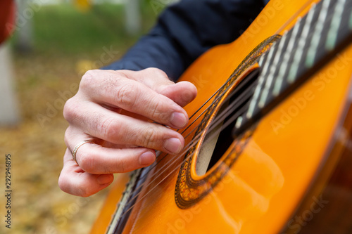 Two friends playing guitars in autumn park - 292946895