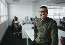 Portrait Of A Successful Smiling Young Professional Businessman Sitting Over Desk In Front Of Colleague Working In Background