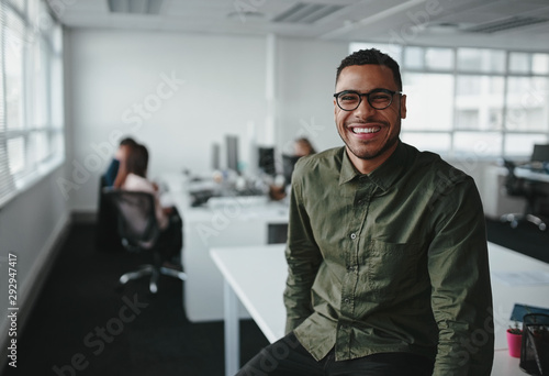 Cuadros en Lienzo Portrait of a successful smiling young professional businessman sitting over des