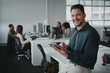 Happy young professional businessman with digital tablet looking at camera against his coworker working in background