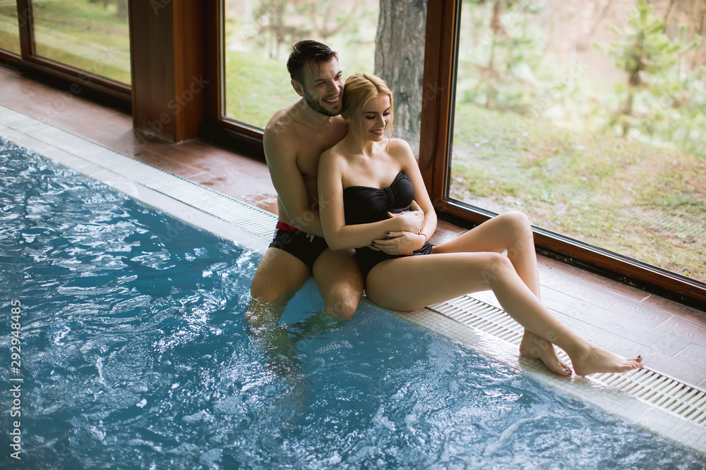 Fototapety, obrazy: Cheerful youthful guy and lady resting by swimming pool in spa