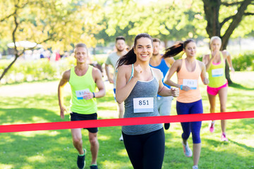fitness, sport and success concept - happy teenage girl winning race and coming first to finish red ribbon over group of sportsmen running marathon with badge numbers at park