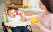Young Woman Feeding Her Cute Toddler In Kitchen