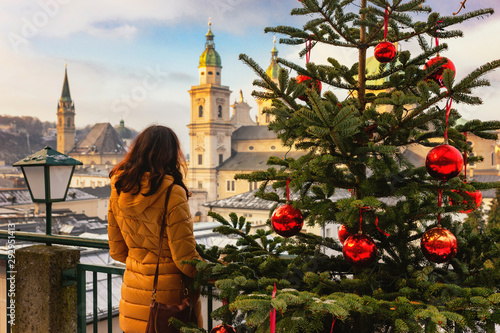 Young woman view from the back stands on the background of sunny Christmas Salzburg, Austria Tapéta, Fotótapéta