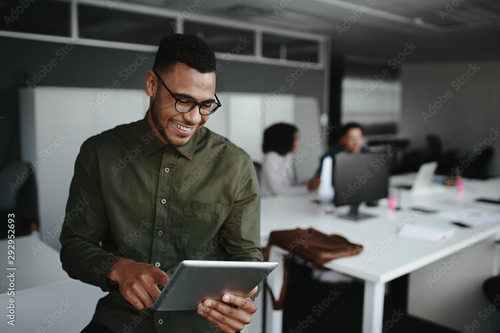 Fototapeta Cheerful young businessman using digital tablet smiling while his colleagues working at the background