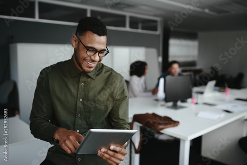 Cheerful young businessman using digital tablet smiling while his colleagues working at the background
