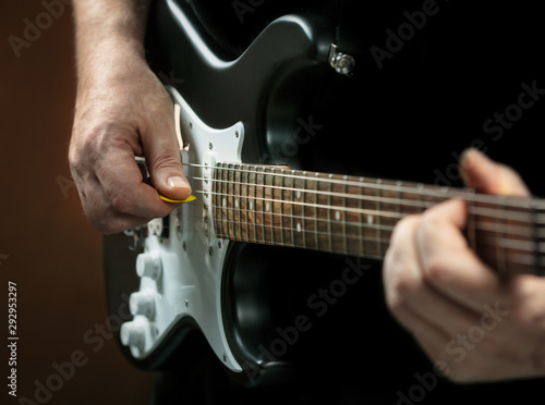 man playing guitar on dark background - 292953297